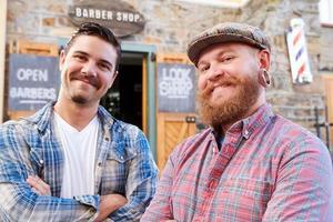 retrato de dois barbeiros hipster em pé fora da loja