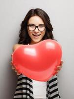 garota atraente e bonita, com um coração nas mãos. foto