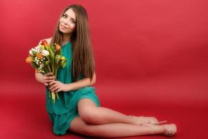 garota linda em um vestido de verão com tulipas