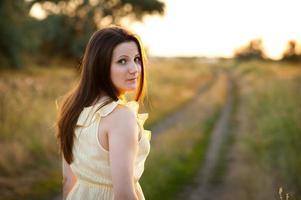 menina de vestido em uma trilha vai ao pôr do sol