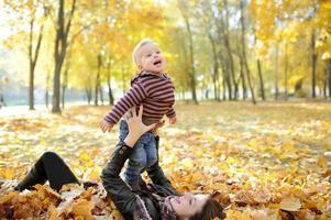 mãe e criança andam no parque outono