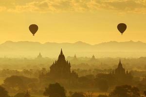 balão sobre pagode bagan com o nascer do sol foto