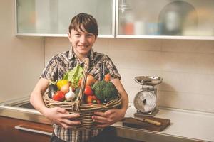 menino prepara legumes na cozinha - pessoas saudáveis vegetarianas foto
