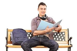 estudante com fones de ouvido, lendo um livro foto