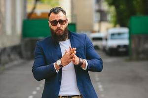 homem barbudo elegante caminha pela cidade