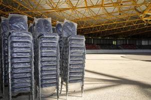 novas cadeiras vazias cobertas de plástico no estádio de patinação no gelo foto