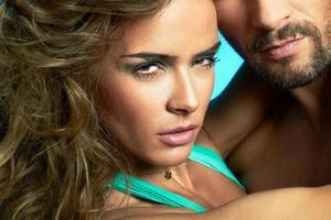 fechar o retrato do jovem casal atraente sobre fundo azul foto