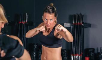 mulher treinando boxe duro no ginásio foto