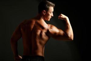 jovem bonito músculo em fundo escuro foto