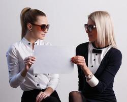 duas meninas segurando papel em branco foto