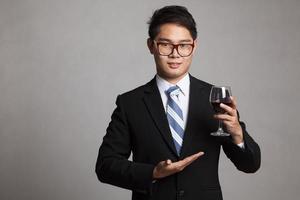 empresário asiático mostra um copo de vinho tinto foto