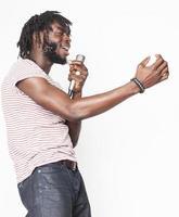 jovem rapaz americano africano bonito cantando emocional com microfone isolado foto