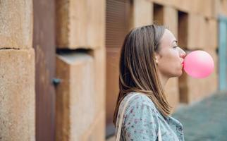 jovem adolescente soprando chiclete rosa foto