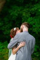 noiva e noivo primeiro beijo na cerimônia de casamento foto