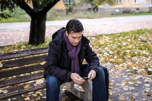 viajante de homem com telefone móvel, sentado no banco foto