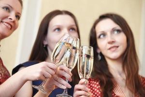 meninas bonitas em uma festa de Natal com copos de champanhe foto