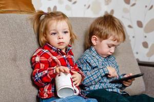 irmão e irmã no sofá com caneca e telefone celular foto
