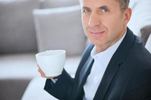 empresário, sorrindo e bebendo uma xícara de café foto