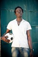 homem africano segurando uma bola de futebol