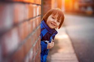 menino adorável, ao lado da parede de tijolos, comendo barra de chocolate