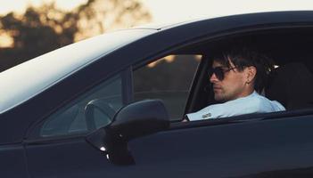 na moda jovem dirigindo seu carro foto