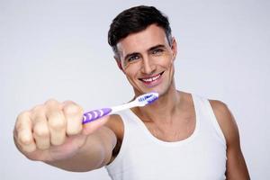 retrato de um homem sorridente segurando a escova de dentes foto