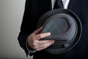 homem segura seu chapéu contra o corpo