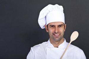 portriat do cozinheiro com colher sobre fundo escuro foto