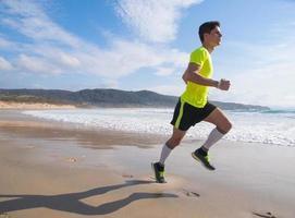 jovem em roupas fitness correndo ao longo da praia foto