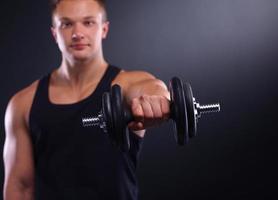 bonito homem musculoso malhando com halteres