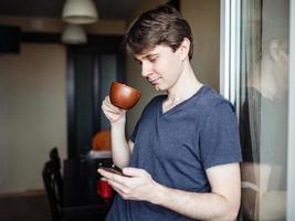 homem tomando café e usando smartphone móvel foto
