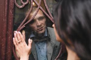 casal olhando um ao outro pela janela foto