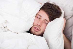 homem dormindo na cama foto
