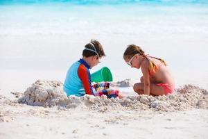 duas crianças brincando com areia foto