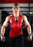 fisiculturista bombeando músculos no crossover