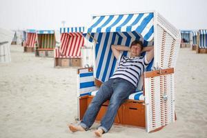 jovem feliz na praia do mar do norte,