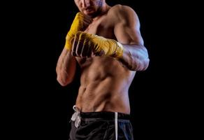 retrato de boxeador chute desportista contra fundo preto. foto