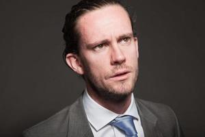 negócios homem cabelos compridos, vestindo terno cinza. foto