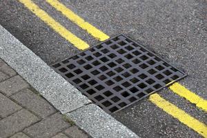 dreno de rua em linha dupla amarela foto