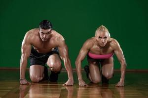 forte casal muscular ajoelhado no chão foto