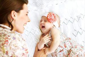 retrato de mãe amorosa feliz e seu bebê ao ar livre foto