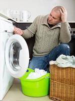 cara triste usando a máquina de lavar roupa