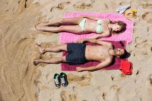 cara e namorada descansando na areia foto
