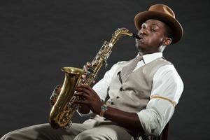 jogador de saxofone jazz americano preto. vintage. tiro do estúdio.