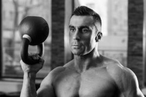 retrato preto e branco de um fisiculturista segurando uma bola de chaleira