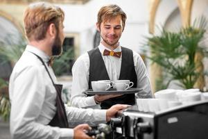 barista fazendo café com garçom foto