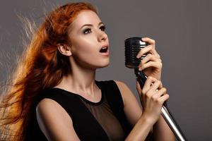 mulher cantando em fundo cinza foto