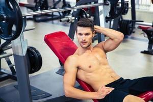 homem deitado no banco no ginásio foto