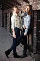 meninas contra uma parede de tijolos foto