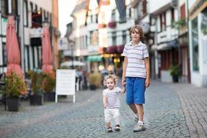 irmão e sua irmãzinha andando no centro histórico da cidade